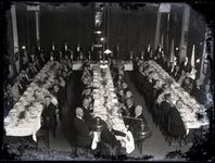 52 Groepsfoto van een groot gezelschap van mannen en vrouwen, aangezeten bij een diner in het Spaarbankgebouw (?)