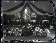 54 Foto van acht mannen voor een versierde wand, gezeten achter een bestuurstafel, in het Spaarbankgebouw te Tiel, ...
