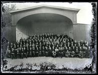 57 Opname van een groep mannen in de muziektent van het Spaarbankgebouw. Het betreft vermoedelijk het Tiels mannenkoor ...