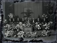 58 Foto van het bestuur van het Tiels mannenkoor met het vaandel in het midden van de bloemen in het Spaarbankgebouw ...