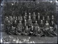 60 Groepsfoto van een aantal onbekende mannen en een vrouw in een tuin