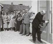 M 12135 Een burgemeester verricht een openingshandeling door met een sleutel een deur te openen