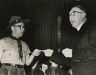 M 404 Pater J.A.A.M. Busch reikt de gouden Jacobsstaf uit aan groepsleider W. Schoots van de St. Maartensgroep te Tiel