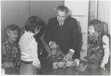 M 8533 Dhr. M. Berends in Ommeren, samen met zittende vrouw en twe kinderen, pakt cadeau uit