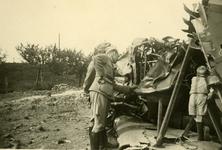 Mobilisatie Kesteren en omgeving : 2 militairen en ene jongetje bekijken een neergestort vliegtuig
