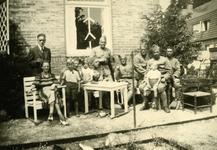 Mobilisatie Kesteren en omgeving : een man, vrouw en 7 militairen met sommigen met een kind op schoot voor een huis