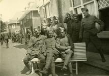 Mobilisatie Kesteren en omgeving : groep militairen zittend op en staand bij een bank voor een rij woonhuizen