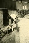 Mobilisatie Kesteren en omgeving : man op erf bezig met schoonmaak in een emmer