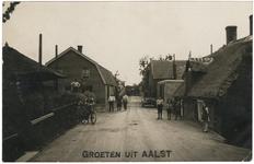 2-10047 Straatgezicht met links op de voorgrond een hooiberg en rechts een auto (M22984) en op de achtergrond een kar ...